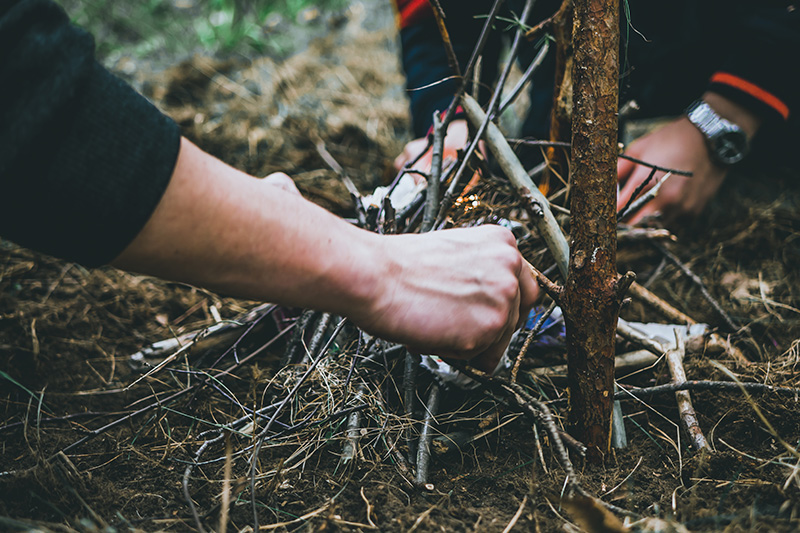 A couple of people setting up a campfire with twigs