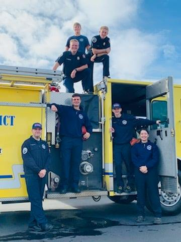 Volunteer fire fighters on yellow fire truck