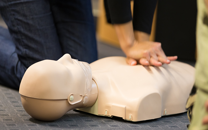 Close up of person practicing CPR on dummy
